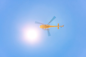Yellow helicopter from below against blue sky with sun