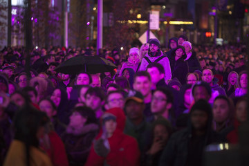 Fans watch Kanye West as he performs with U2 during a surprise concert in support of World AIDS Day in Times Square in New York