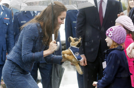 Catherine, the Duchess of Cambridge, receives a toy dog from a young girl as she tours with her husband, Britain's Prince William, the Royal New Zealand Police College in Wellington