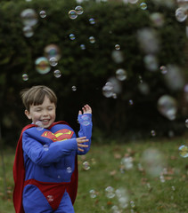 A boy dressed as Superman plays with a bubble machine at the Flint family's annual Halloween block party in Silver Spring, Maryland