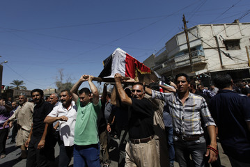 Mourners carry a victim's coffin during a mass funeral for the victims of Wednesday's bomb attacks on a Shi'ite mosque in Baghdad