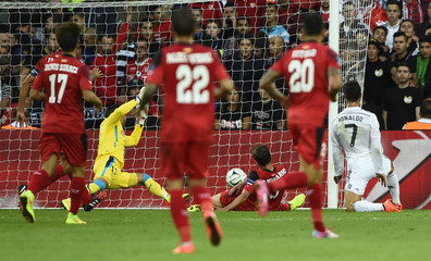 Real Madrid's Ronaldo scores a goal past Sevilla's Navarro and goalkeeper Beto during the UEFA Super Cup final soccer match at Cardiff City stadium