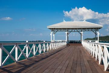 Wooden white pavilion on sunny day, seacoast skyline