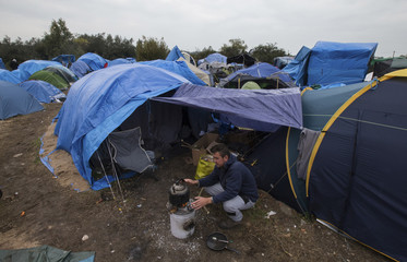 """A migrant heats water outside his tent in the """"New Jungle"""" make-shift camp as unseasonably cool  temperatures arrive in Calais"""
