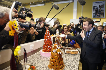 French Economy Minister Emmanuel Macron offers cakes to news photographers as he visits a pastry school at the Campus des Metiers et de l'Entreprise in Bobigny
