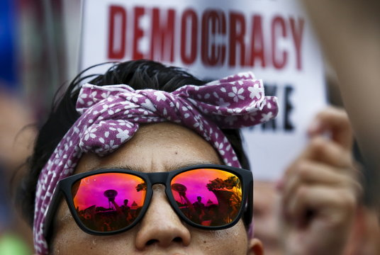 A rally against Japan's Prime Minister Shinzo Abe's security bill is reflected in a protester's sunglasses outside the parliament in Tokyo