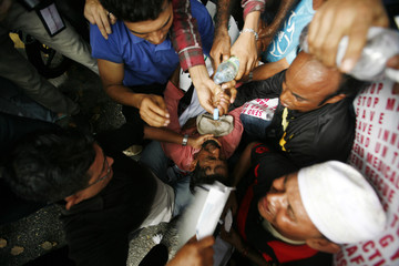 An ethnic Rohingya from Myanmar and living in Malaysia, receives help after fainting during a rally calling for a stop to the killings and violence toward the Muslim Rohingyas in Myanmar, near the Myanmar embassy in Kuala Lumpur
