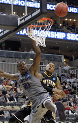 Kansas State University's Henriquez and University of Southern Mississippi's Bolden collide under the basket in Pittsburgh