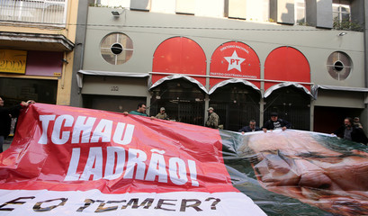 """Brazilian federal police officers stand in front of the headquarters of Workers' Party as supporters of PT hold a banner with a picture of suspended House Speaker Cunha, that reads, """"Bye robber!"""" and """"And Temer?"""" in Sao Paulo,"""