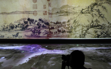 A reporters takes photos of an audio/visual interpretation of a painting entitled 'Dwelling in the Fuchun Mountains' by Chinese painter Huang Gongwang at the National Palace Museum in Taipei