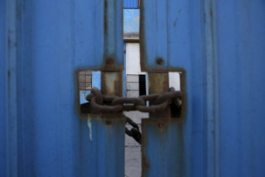 A gate of a closed steel factory is seen locked by chain lock in Tangshan