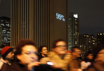 Occupy Wall Street demonstrators march over the Brooklyn Bridge as a 99% sign is projected onto the side of the Verizon Building in New York