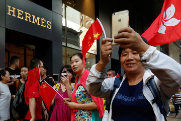 Visitors from mainland China watch a march by pro-China supporters at Tsim Sha Tsui shopping district to celebrate China's National Day in Hong Kong