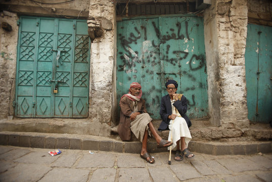 Men sit next to closed shops in the Old City of Ibb, the provincial capital of Yemen's central province of Ibb
