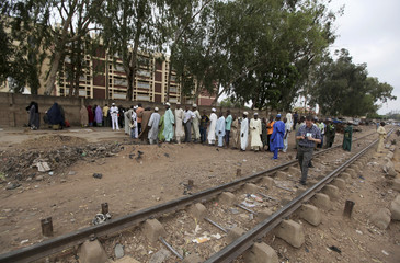 People queue to vote at a polling unit near a railway track in Angwa Shanu village