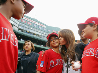 Entertainer Paula Abdul kisses a Little Leaguer before the MLB Interleague baseball game between the Nationals and the Red Sox at Fenway Park in Boston