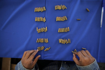 "A city employee counts 22 mm calibre bullets during the ""Voluntary Disarmament Programme"" in San Nicolas in Monterrey"