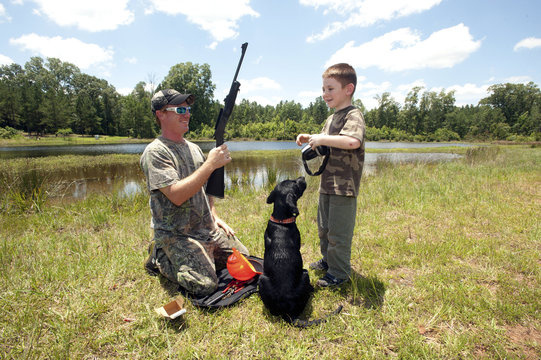 Jeremy Chavez helps his son with target practice before a wild hog hunt at Great Southern Outdoors Wildlife Plantation in Union Springs