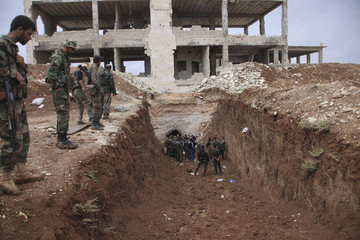 Forces of Syria's President Assad stand in a trench near the glass factory in Jubaila village in the countryside of north-east Aleppo after regaining control of the area