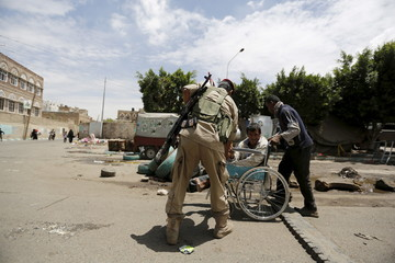 Houthi militant helps a man with a wheelchair pass a checkpoint in Yemen's capital Sanaa