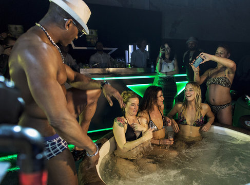 A male stripper performs while movie fans enjoy a hot bubble bath while watching a movie at the Hot Tub Movie Club in Amsterdam