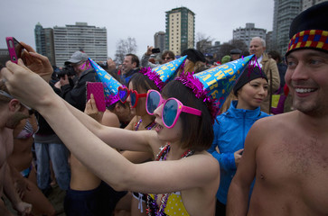 Participants take pictures of people running into English Bay during the 94th annual New Year's Day Polar Bear Swim in Vancouver