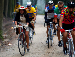 """Cyclists ride vintage bicycles on gravel roads during the Strade Bianche section of the """"Eroica"""" cycling race of old bikes in Gaiole in Chianti"""