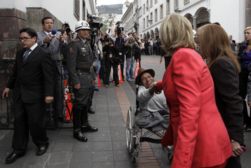 U.S. Secretary of State Hillary Clinton shakes hands with a handicapped beggar shortly after her arrival at the Carondelet Palace in Quito