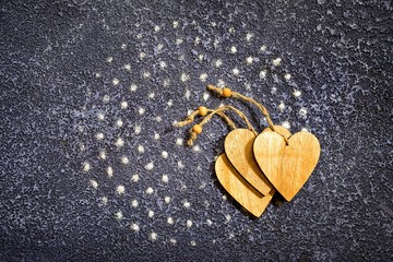 Dots of salt lined in a circle on a dark blue cement background and three wooden hearts with copy space as a food background
