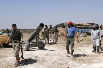 Free Syrian Army fighters walk near a locally made weapon in the southern Idlib countryside
