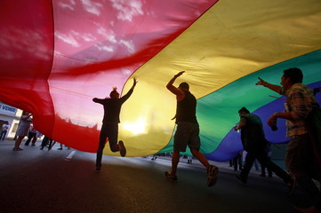 Revellers run under a huge rainbow flag during a Gay Pride parade in Ciudad Juarez