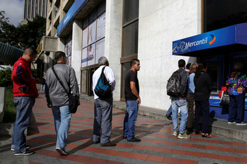 People line up to withdraw cash from an automated teller machine (ATM) outside a Banco Mercantil branch in Caracas