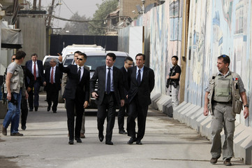 France's Industry Minister Christian Estrosi walks past the french Embassy in Baghdad