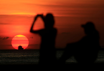 A group of friends are silhouetted as they take a photograph while watching the sun set along the coast of Manila bay in Metro Manila