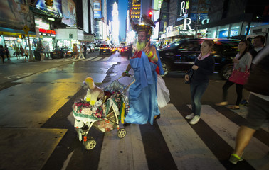 A man with a parrot on his head and a dog in a stroller, with his beard dyed yellow, gestures while walking through Times Square in New York
