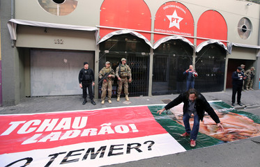 """Brazilian federal police officers stand in front of the headquarters of Workers' Party as a supporter of PT walks over a banner with a picture of suspended House Speaker Cunha, that reads, """"Bye robber!"""" and """"And Temer?"""" in Sao Paulo,"""
