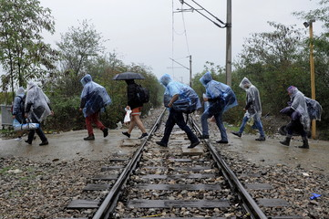 A group of Syrian refugees wearing plastic raincoats to protect from heavy rainfall, walk across a railway line into Macedonia near the Greek village of Idomeni