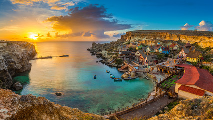 Il-Mellieha, Malta - Panoramic skyline view of the famous Popeye Village at Anchor Bay at sunset with traditional Luzzu boats, beautiful colorful clouds and sky Fototapete
