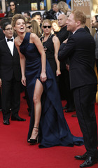 Actress Amber Heard laughs as actor Jesse Tyler Ferguson makes a joke at the 71st annual Golden Globe Awards in Beverly Hills