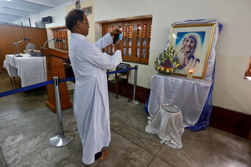 A man takes a photograph of a religious icon of Mother Teresa ahead of her canonisation ceremony