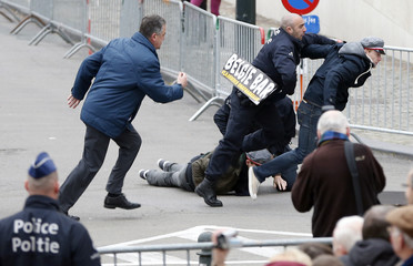 Belgian police officers arrest Flemish separatists after they shout anti-monarchy slogans outside a Te Deum mass to celebrate King's Day in Brussels