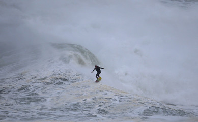 Big-wave surfer Andrew Cotton of Britain drops in on a large wave at Praia do Norte