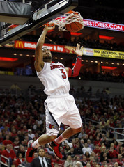 University of Louisville's Peyton Siva dunks the basketball over Providence College's defense the first half of play in their NCAA basketball game a Yum! Center in Louisville