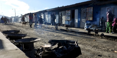 People walk at the witch market, where witch doctors have their stalls, in El Alto
