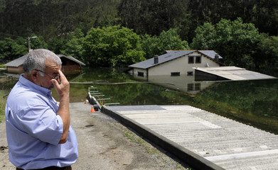 A man gestures next to his flooded home after heavy rains in the Spanish northern town of Bao