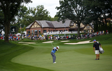 Woods of the U.S. hits from the 13th fairway with the clubhouse in background during a practice round for the 2013 PGA Championship golf tournament at Oak Hill Country Club in Rochester