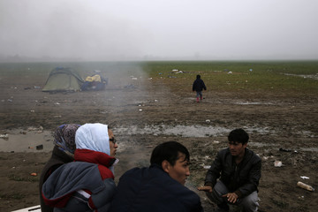 Afghan migrants warm themselves next to a bonfire at a makeshift camp for refugees and migrants at the Greek-Macedonian border near the village of Idomeni