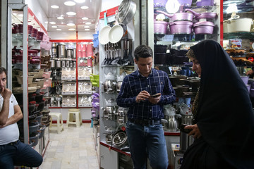 A shop keeper uses his smartphone to follow the presidential election results, at the Grand Bazaar in central Tehran