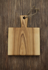 Wooden rustic background with a brown cutting board. Top view, free space