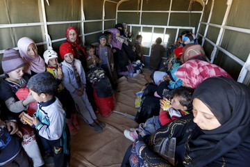 Syrian refugees fleeing the violence in their country sit in a Jordanian army vehicle, after they crossed into Jordanian territory